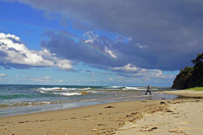 A rainbow sharing a secret with a man. On the beach, near Wonthaggi, Victoria, Australia