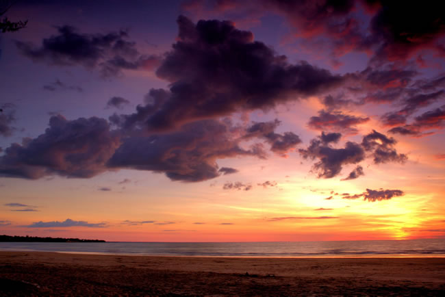 Dramatic cloudscape accentuates the setting sun. Casuarina Beach, Darwin, Australia
