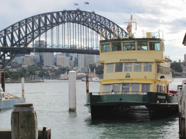 The Sydney Harbour Bridge with a Sydney ferry in the foreground, as seen from Circular Quay. Sydney, New South Wales, Australia.