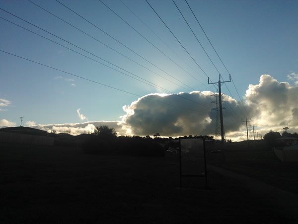 Dramatic cloudscape hides the setting sun. Augustine's Dam, Highton, Geelong, Australia on a sunny winter's afternoon.